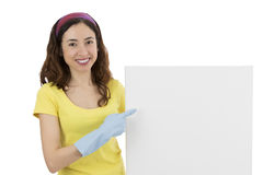 Cleaning woman pointing to blank advertising board. Friendly cleaning woman showing a blank marketing poster Royalty Free Stock Photos