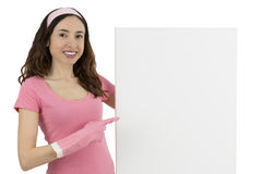 Cleaning woman showing a blank advertising poster. Smiling young caucasian cleaning woman pointing out to a white advertisement poster Stock Image