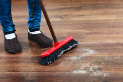 Cleaning woman sweeping wooden floor. Cleanup housework concept. Closeup broom and female foots. Cleaning woman sweeping wooden floor Royalty Free Stock Photography