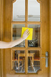 Cleaning a wood and glass door Stock Photography