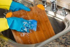 Cleaning Wooden Cutting board inside of Kitchen Sink with sponge stock photos