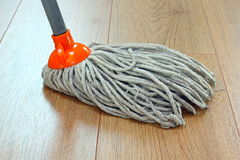 Cleaning wooden floor. Detail of a mop cleaning wooden floor stock photos