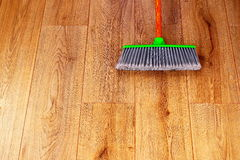 Cleaning wooden floor with green plastic broom Royalty Free Stock Photos