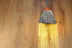 Cleaning wooden floor with a mop Royalty Free Stock Photography