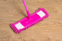 Cleaning wooden floor with pink mop Royalty Free Stock Photos