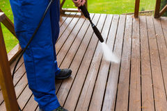 Cleaning wooden terrace with high pressure washer. Cleaning wooden plank terrace with high pressure washer royalty free stock images