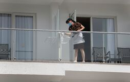 A cleaning worker wearing protective mask clean a glass in a balcony in a hotel in Mallorca detail