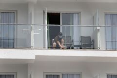 A cleaning worker wearing protective mask clean a glass in a balcony in a hotel in Mallorca wide