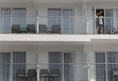 A cleaning worker wearing protective mask clean a glass in a balcony in a hotel in Mallorca