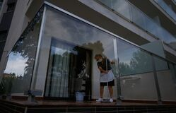A cleaning worker wearing protective mask scrub the floor of a hotel balcony room