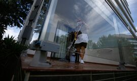 A cleaning worker wearing protective mask scrub the floor of a hotel balcony room wide