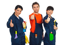 Cleaning workers giving thumbs up. Cleaning workers in a row holding cleaning products and giving thumbs up isolated on white background stock image