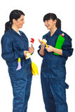 Cleaning workers women having conversation. Two happy cleaning workers women having conversation and holding cleaning products isolated on white background royalty free stock image