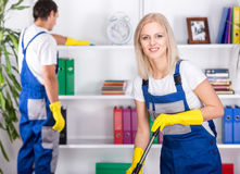 Cleaning. Young couple professional cleaners are cleaning the office Royalty Free Stock Images