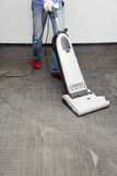 Cleans the carpet. Worker cleans the carpet, vacuum cleaner Royalty Free Stock Photos