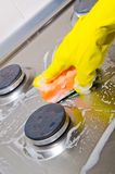 Cleans a kitchen gas cooker Royalty Free Stock Photos