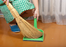 Cleans trash with a dustpan Royalty Free Stock Image