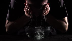 Cleansing concept. Symbolic concept: a man cleansing himself with water. purification. Captured at 60fps. front view stock video footage