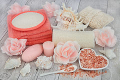 Cleansing and Exfoliating Accessories. Cleansing spa accessories with himalayan salt, rose soap petals and exfoliating bathroom products on distressed white wood Stock Image