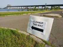 Cleanup This Way, Newark Bay Bridge, Bayonne, NJ, USA. Sign directing volunteers to the location of the cleanup. In the background, the Newark Bay Bridge. This stock photos