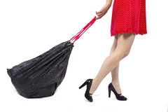 Cleanup. Woman cleaning up and holding a black trashbag Royalty Free Stock Photography