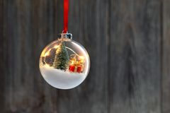 Clear Ball Ornament with christmas tree and small gift. Clear Ball Ornament with christmas tree, small gift and christmas light inside stock photography