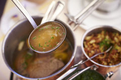 Clear beef soup in a ladle over a pot Royalty Free Stock Image