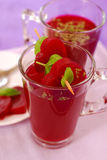 Clear beet soup in glass. Clear beet soup (red borscht)in glass decorated with heart shaped slices and basil royalty free stock photo
