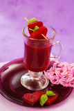 Clear beet soup in glass. Clear beet soup (red borscht)in glass decorated with heart shaped slices and basil royalty free stock photography
