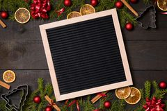 Clear black felt letter board flatlay on dark rustic wood table with Christmas decoration and fir tree boarder. Top view with. Free text copy space stock photography