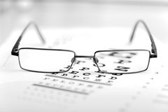 Clear Black modern glasses on eye sight test chart. Clear Black modern glasses on a eye sight test chart Stock Images