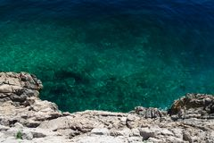 Clear blue-green sea with a rocky cliff Royalty Free Stock Photography