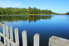 A clear blue lake with a wooden dock surrounded by green pine forest in the northern woods of Minnesota. Royalty Free Stock Photo