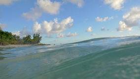 Clear blue ocean water and tropical island. Slow motion shot of wavy surface of clear blue ocean with view to the coast of tropical island stock video