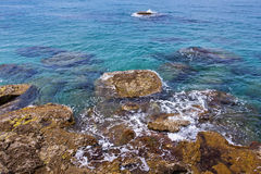 Clear blue sea with rocky shore Stock Photo