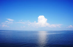 Clear blue sea surface with ripples and sky with fluffy clouds.  Stock Image