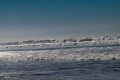 Clear blue skies and sunlight with Atlantic Ocean waves crashing onto sand beach with no people in Agadir, Morocco, Africa royalty free stock photo