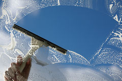 Clear blue sky. Window cleaner using a squeegee to wash a window Stock Image