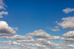 Clear blue sky background with clouds. Vibrant nature scene. Natural frame of white fluffy clouds. Copyspace.  stock photo