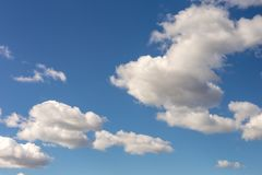 Clear blue sky background with some fluffy white clouds. Vibrant nature scene royalty free stock image