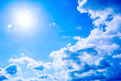 Clear blue sky with fluffy clouds and sunbeams Royalty Free Stock Photo