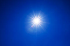 Clear blue sky sun light with Real Lens flare out of focus Royalty Free Stock Photos