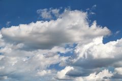 The clear blue sky with white clouds, closeup / Very fine weather with stratocumulus and cumulus clouds on a summer day. The clear blue sky with white clouds stock photo
