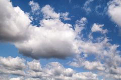 The clear blue sky with white clouds, closeup / Very fine weather with stratocumulus and cumulus clouds on a summer day. The clear blue sky with white clouds stock photos