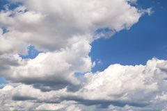 The clear blue sky with white clouds, closeup / Very fine weather with stratocumulus and cumulus clouds on a summer day. The clear blue sky with white clouds stock photography