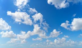 Clear blue sky with white fluffy clouds. Nature background stock photography