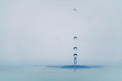 Clear blue water drop with ripple on surface stock photo
