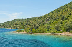 Clear blue water at green mountainous island Stock Images