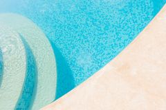 Clear blue water in the pool. Part of the pool closeup. Step int. O the water and finish the pool bottom slab-mosaic royalty free stock images