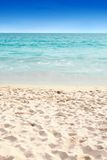 Clear blue water and soft sandy beach Stock Images